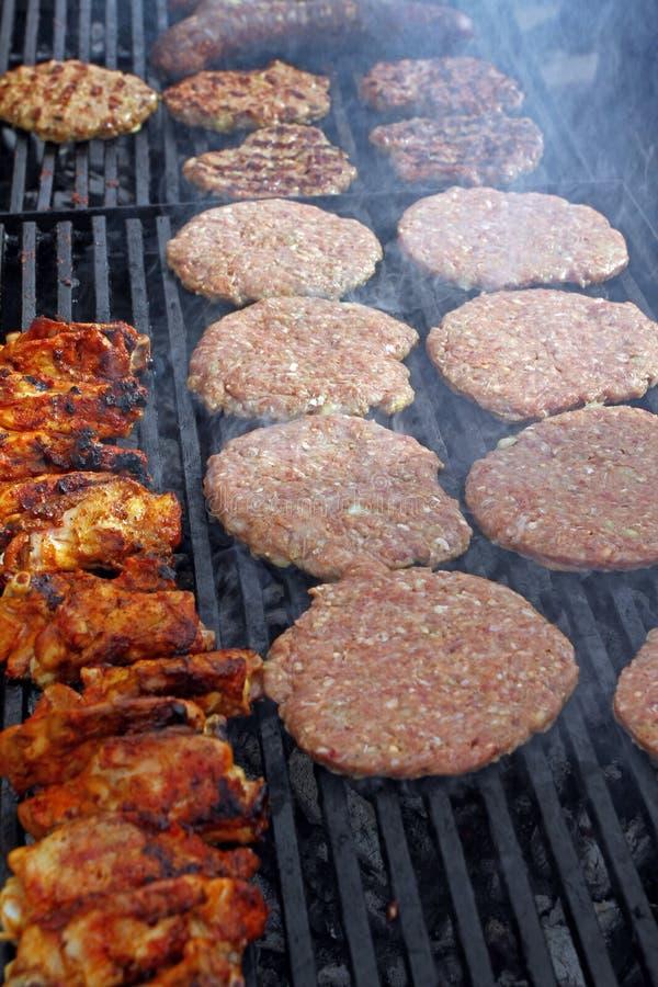 Griller des saucisses, hamburgers, bifteck de porc sur le gril de gaz de barbecues pour la partie Hot-dogs, saucisses et hamburge photos stock