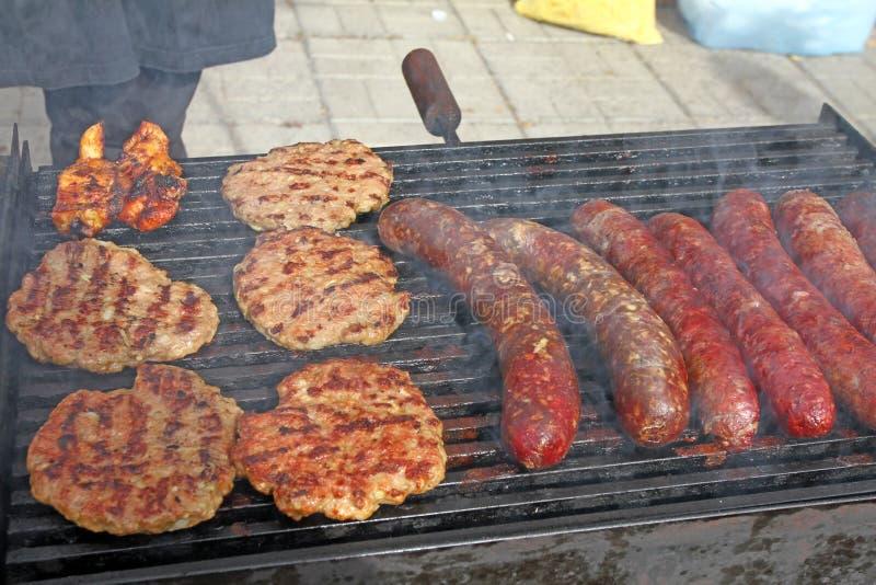 Griller des saucisses, hamburgers, bifteck de porc sur le gril de gaz de barbecues pour la partie Hot-dogs, saucisses et hamburge photographie stock