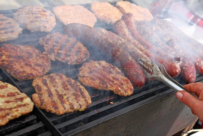Griller des saucisses, hamburgers, bifteck de porc sur le gril de gaz de barbecues pour la partie Hot-dogs, saucisses et hamburge photo stock