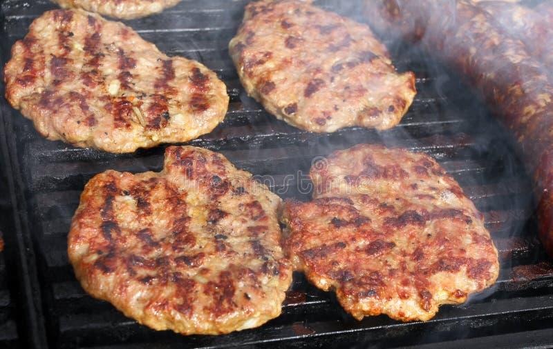 Griller des saucisses, hamburgers, bifteck de porc sur le gril de gaz de barbecues pour la partie Hot-dogs, saucisses et hamburge images stock