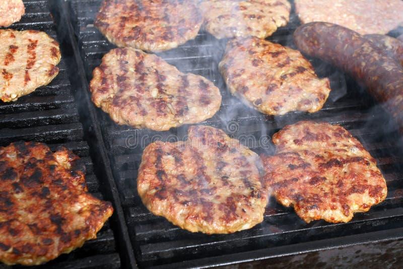 Griller des saucisses, hamburgers, bifteck de porc sur le gril de gaz de barbecues pour la partie Hot-dogs, saucisses et hamburge image libre de droits