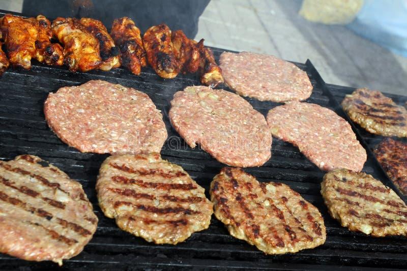 Griller des saucisses, hamburgers, bifteck de porc sur le gril de gaz de barbecues pour la partie Hot-dogs, saucisses et hamburge photo libre de droits