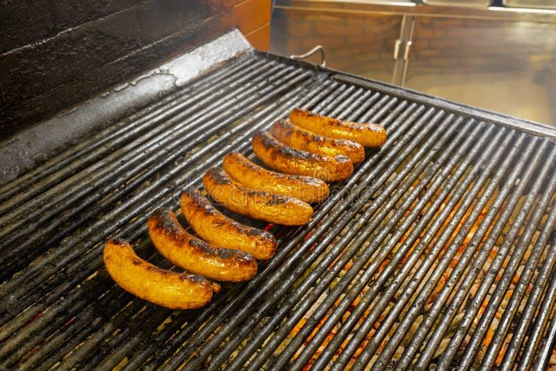 Griller des saucisses sur le gril photographie stock libre de droits