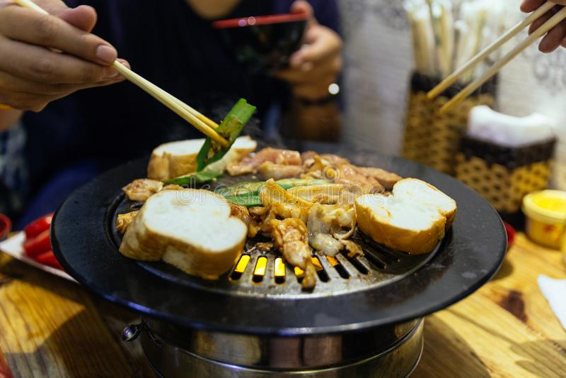 Griller le porc coupé en tranches, les légumes et le pain de BBQ sur la casserole chaude par la baguette au restaurant à Hanoï, V photo stock