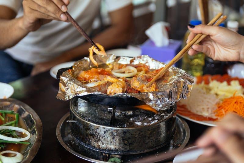 Griller les saumons et l'oignon sur l'aluminium au-dessus de la casserole chaude au restaurant dans la PA de SA, le Vietnam photo stock
