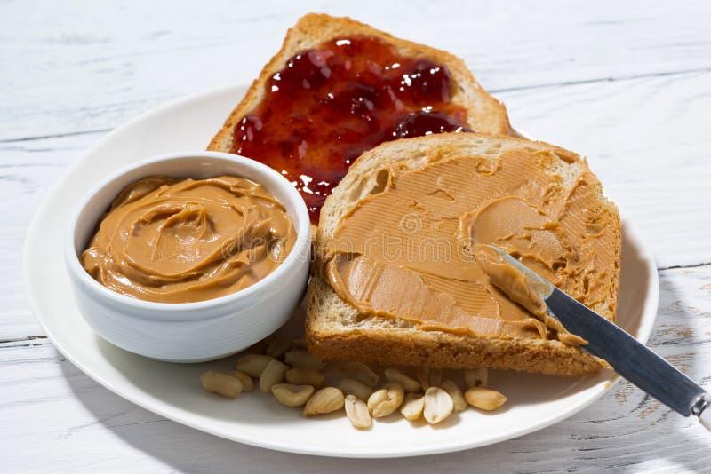 grillez avec le beurre et la confiture d'arachide pour le petit déjeuner sur la table blanche photo stock