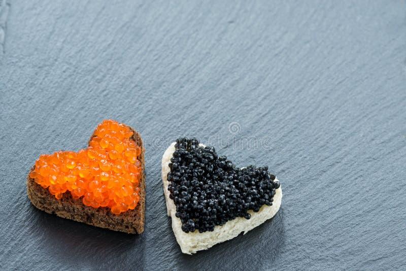 Grillez avec le caviar rouge et noir sous forme de coeur sur l'obscurité photo stock