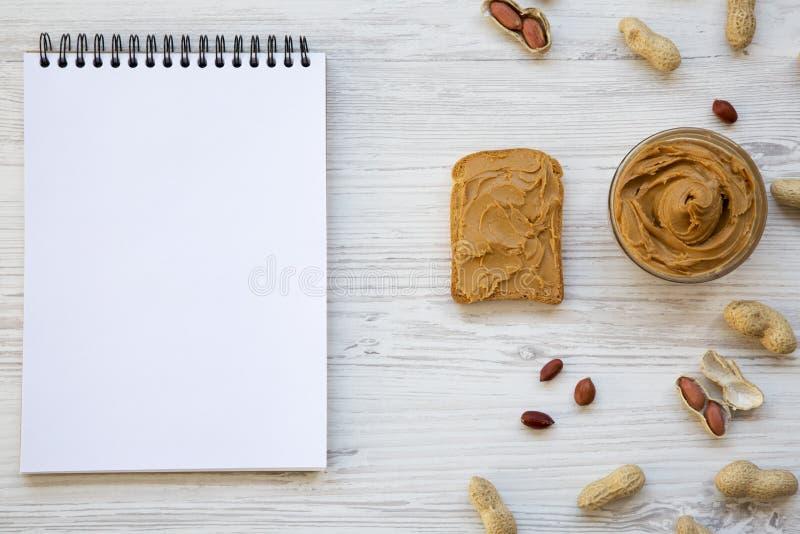Grillez, bol de beurre d'arachide, arachides et carnet sur un fond en bois blanc, vue supérieure image stock