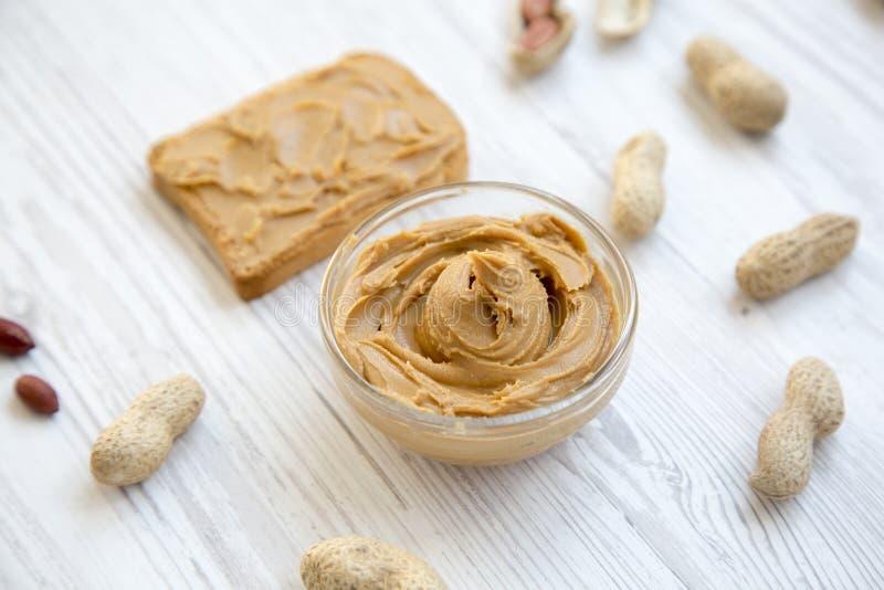 Grillez, bol de beurre d'arachide et arachides dans les coquilles sur un fond en bois blanc, images libres de droits
