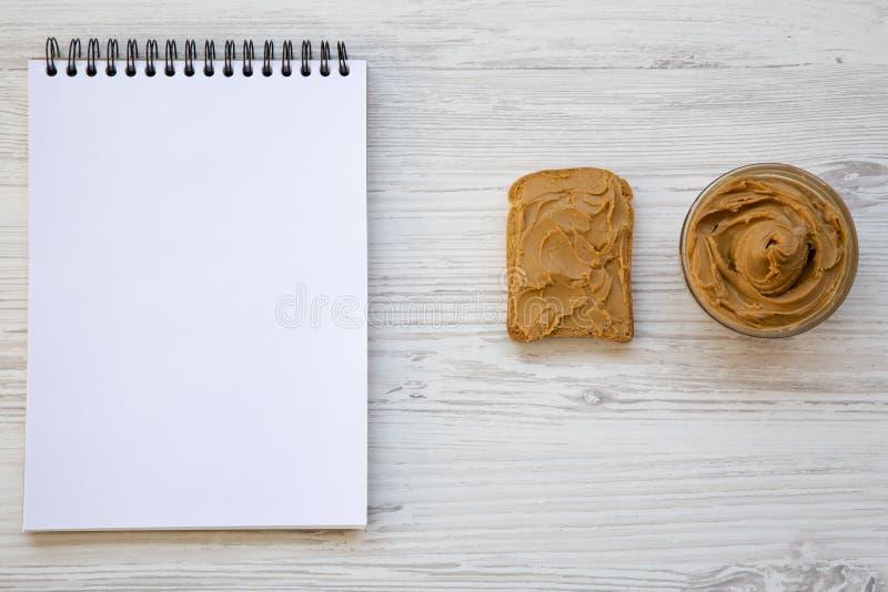 Grillez, bol de beurre d'arachide et carnet sur un fond en bois blanc, vue supérieure photographie stock libre de droits