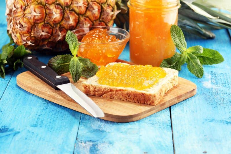 Grillez le pain avec de la confiture faite maison d'ananas ou la confiture d'oranges sur la table a servi avec du beurre pour le  images stock