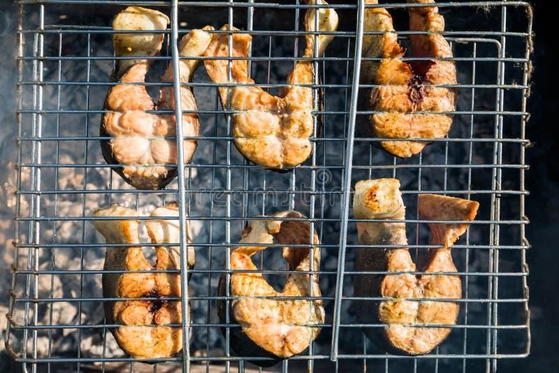 Grillez les poissons sur le feu Saumons images stock