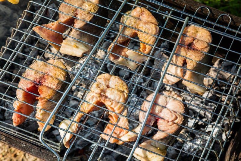 Grillez les poissons sur le feu Saumons photo stock