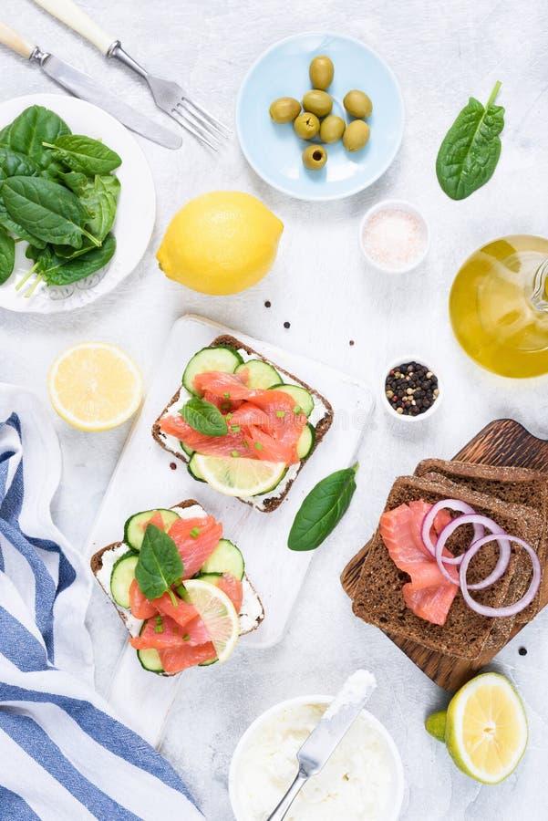 Grillez les sandwichs avec le fromage de saumon et fondu, les olives et le concombre sur la table blanche photo libre de droits