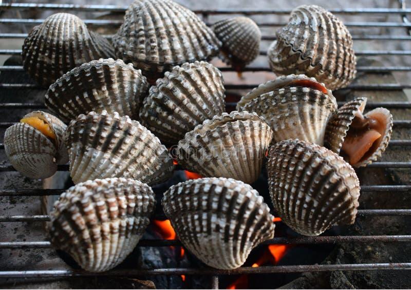 Grillez tout entier le gril faisant cuire des fruits de mer, coquillages de coque faisant cuire sur le gril photo libre de droits