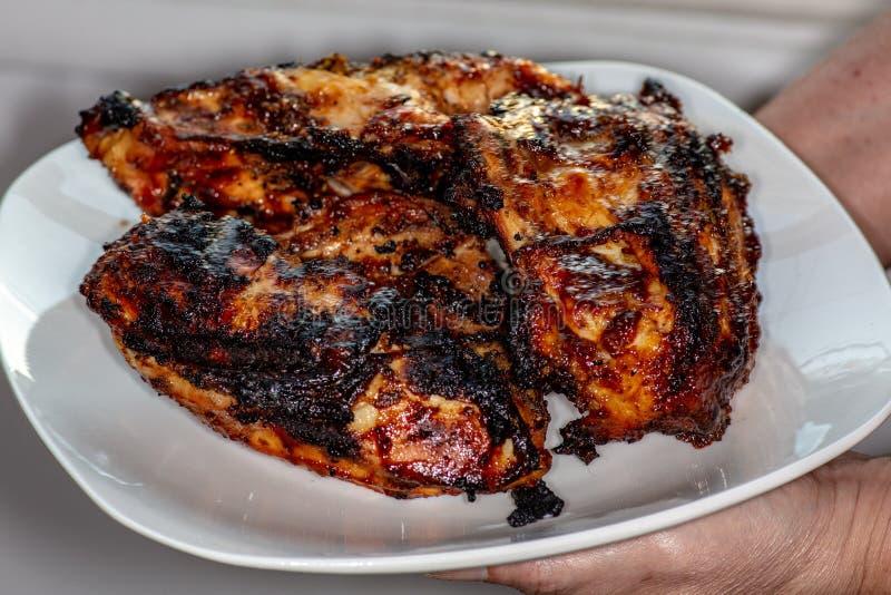 Grillez tout entier les blancs de poulet frais outre du gril d'un plat blanc sur la table de cuisine attendant pour être mangé images stock