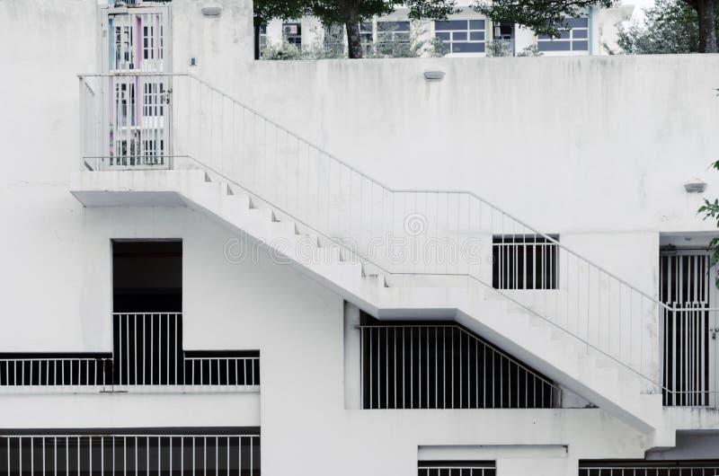 Grillfenster von verschiedenen Formen und von Größen an der weißen Betonmauer, ein externes Treppenhaus auf Gebäude, umfaßtes Par lizenzfreies stockfoto