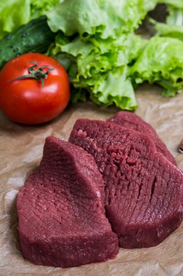 Grillfest för rått kött med träyttersida för nya grönsaker Mat biff, nötköttbbq, tomater, peppar, kryddor för att laga mat arkivfoton