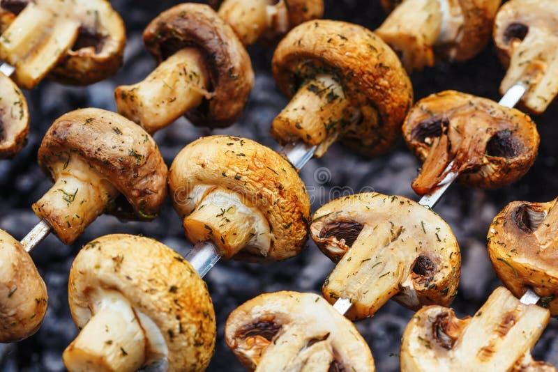 Grillfeststeknålar med grillad champignonchampinjonkebab i en fyrpanna royaltyfri foto
