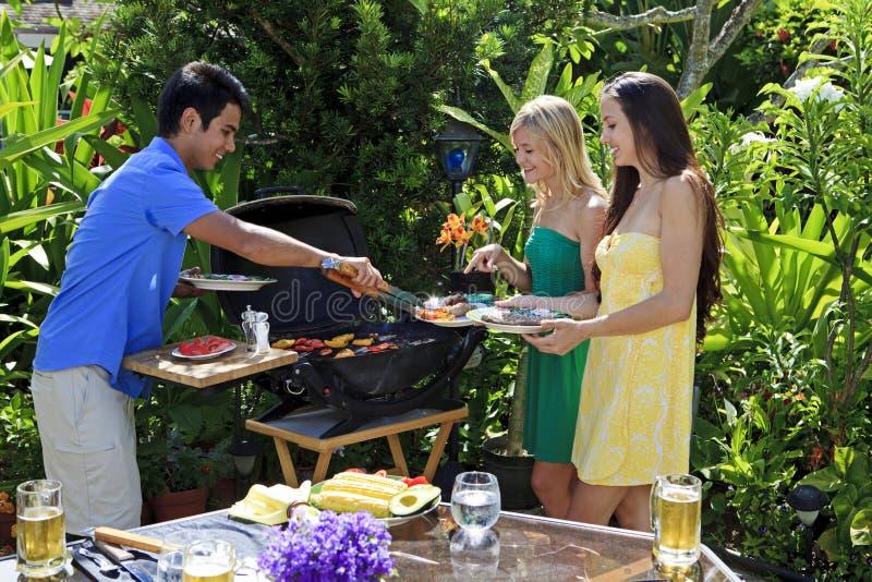 grillfestvänner som har lunch tre royaltyfri bild
