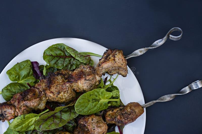 Grillfleisch auf Aufsteckspindeln auf einer Platte mit Kopfsalat Fleisch auf Aufsteckspindeln Ansicht von oben Dunkler Hintergrun stockfoto