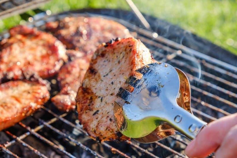 Grillgrill mit kulinarischem Zangen-ANG-Fleisch Oben gesetzt auf Grasabschluß lizenzfreie stockbilder