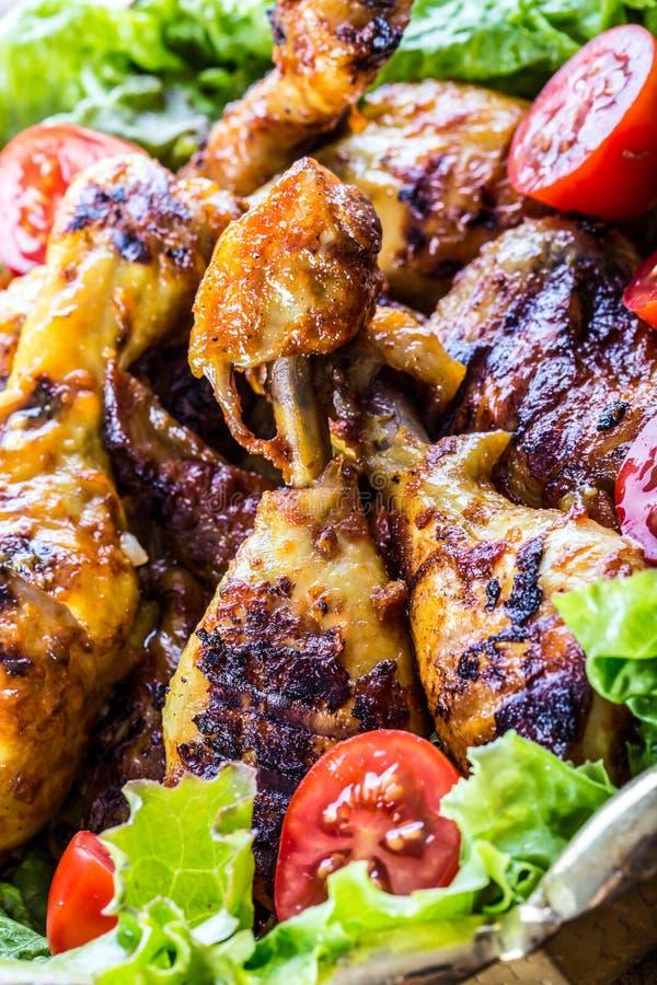 grilling κοτόπουλο που ψήνεται στη σχάρα ψημένα στη σχάρα κοτόπουλο πόδια Ψημένα στη σχάρα πόδια κοτόπουλου, ντομάτες μαρουλιού κ στοκ εικόνες
