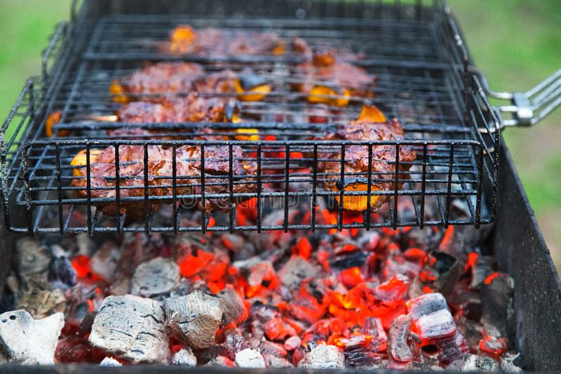 Grilling meat on metal grid on hot coals. royalty free stock photos