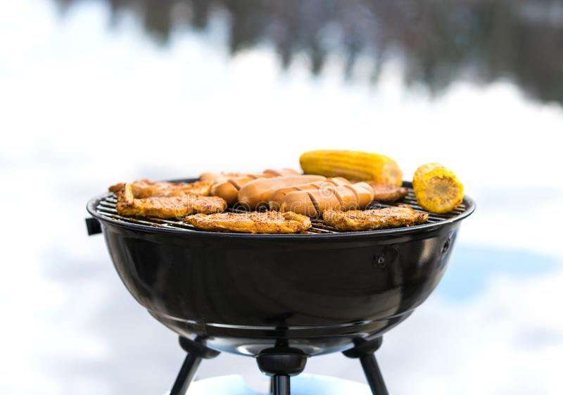 Grilling at the beach. Food cooking on a charcoal kettle grill stock photography