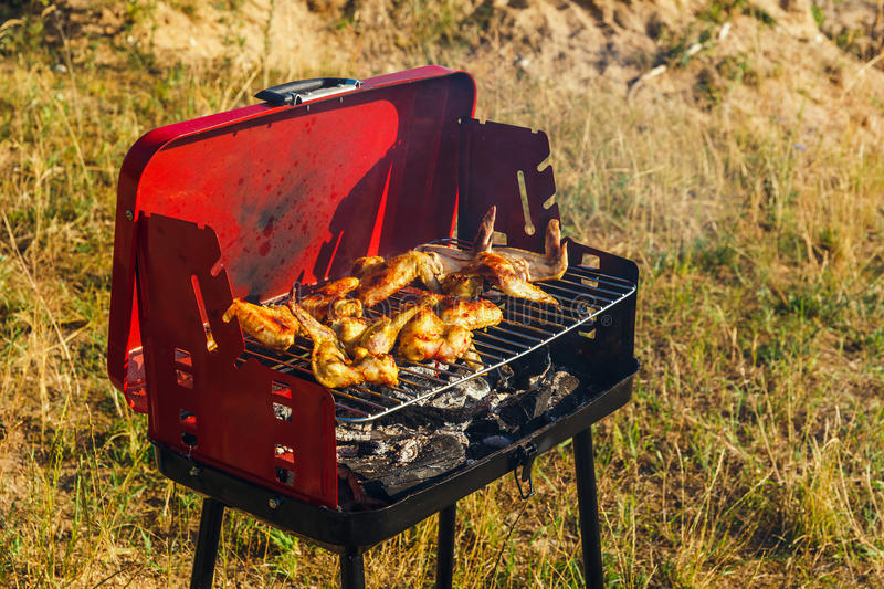 Grilling chicken breast with a charcoal grill stock images