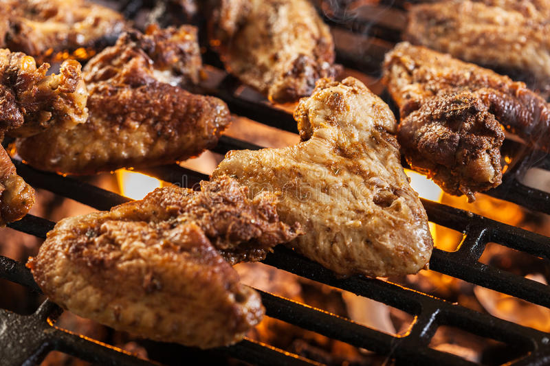 Grilling chicken wings on barbecue grill. Selective focus stock photos