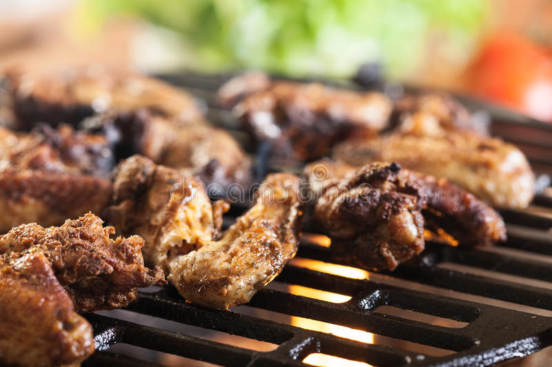 Grilling chicken wings on barbecue grill. Selective focus stock image