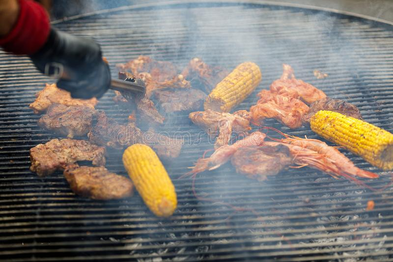 Grilling corn cobs, chicken legs and shrimp. Process of grilling corn cobs, chicken legs and shrimp stock photography