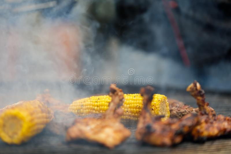 Grilling corn cobs, chicken legs and shrimp. Process of grilling corn cobs, chicken legs and shrimp royalty free stock photo