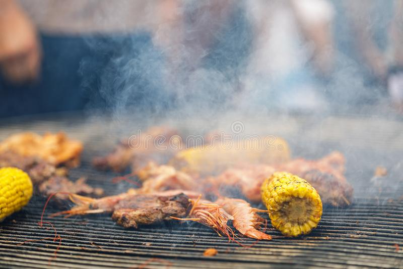 Grilling corn cobs, chicken legs and shrimp. Process of grilling corn cobs, chicken legs and shrimp stock image