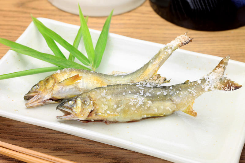 Grilling fish with salt of the sweetfish. This is a grilling fish with salt of the sweetfishs with a Japanese dish stock images