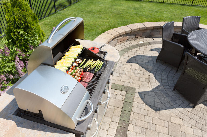 Grilling food on an outdoor gas barbecue stock photography
