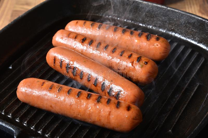 Grilling hot dogs. Stuffed with cheese and jalapenos on a cast iron grill stock images
