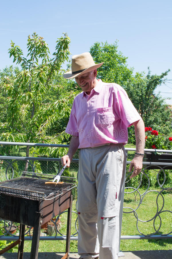 grilling man senior στοκ εικόνες