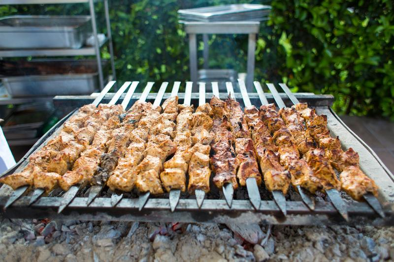 Grilling marinated shashlik on a grill. Shish kebab. BBQ, barbecue on the background of green spaces stock images
