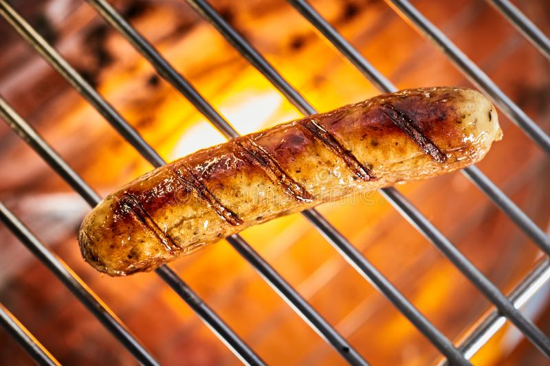Grilling one sausage on barbecue grill. Grilling one delicious meat sausage on hot barbecue grill, viewed in full frame close-up from above royalty free stock photography