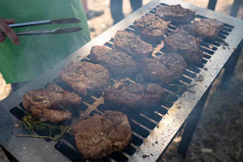 Grilling pork meat with barbecue stuff. Horizontal close up shot with a selective focus royalty free stock photography