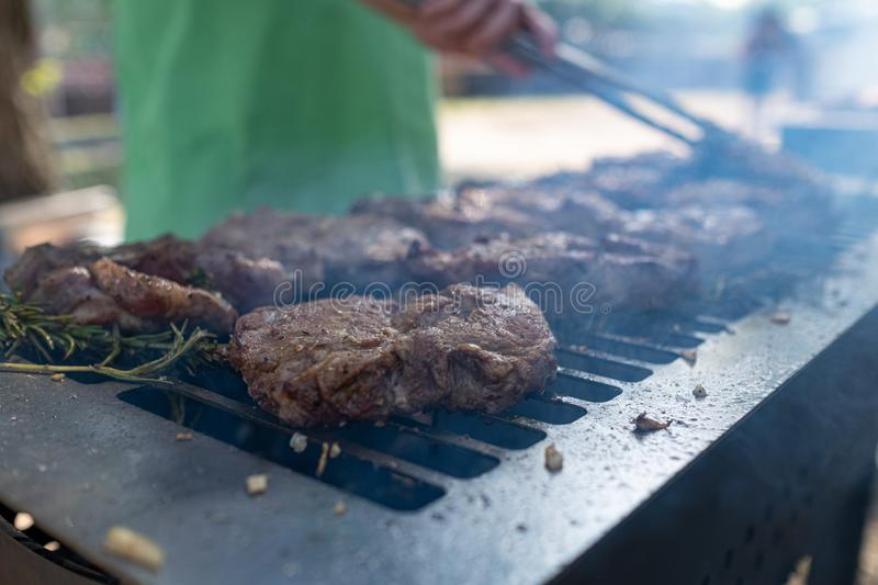 Grilling pork meat with barbecue stuff. Horizontal close up shot with a selective focus stock images