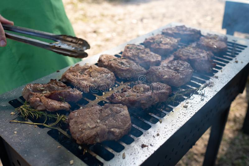 Grilling pork meat with barbecue stuff. Horizontal close up shot with a selective focus royalty free stock image