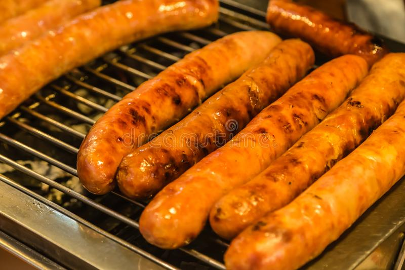 Grilling pork sausages on barbecue grill closeup view. Grilling sausages on barbecue grill closeup view stock photography