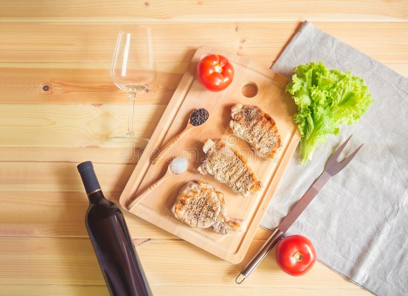 Grilling pork steaks on cutting board, bottle of red wine, empty wineglass, fork and salad leaves. Top view, copy space royalty free stock image