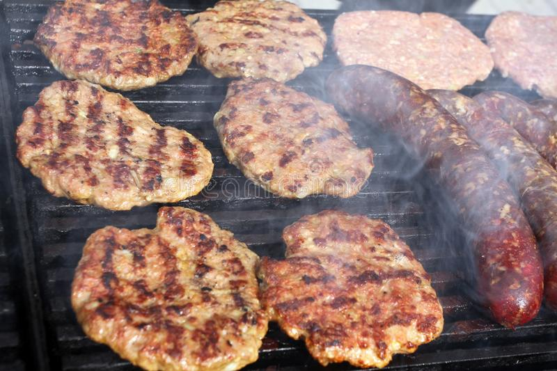 Grilling sausages, burgers, pork steak on barbecues gas grill for party. Hot dogs,sausages and hamburgers on a barbeque, bbq. Smok stock image