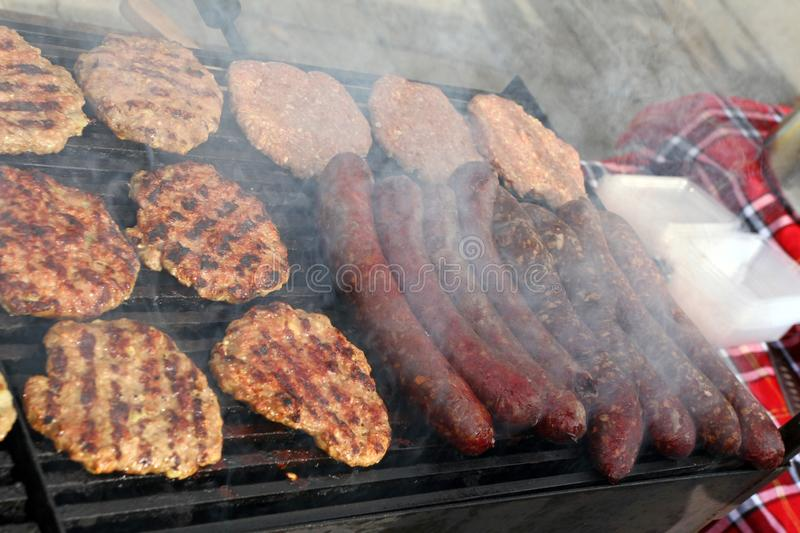 Grilling sausages, burgers, pork steak on barbecues gas grill for party. Hot dogs,sausages and hamburgers on a barbeque, bbq. Smok royalty free stock photos