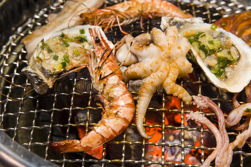 Grilling seafood of shrimp, octopus and oysters on hot charcoal royalty free stock photo