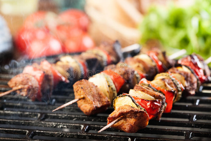 Grilling shashlik on barbecue grill stock images